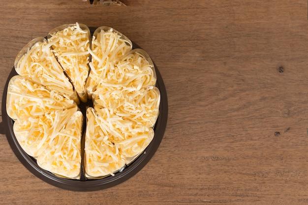 Gros plan du gâteau au fromage sur fond de bureau en bois.