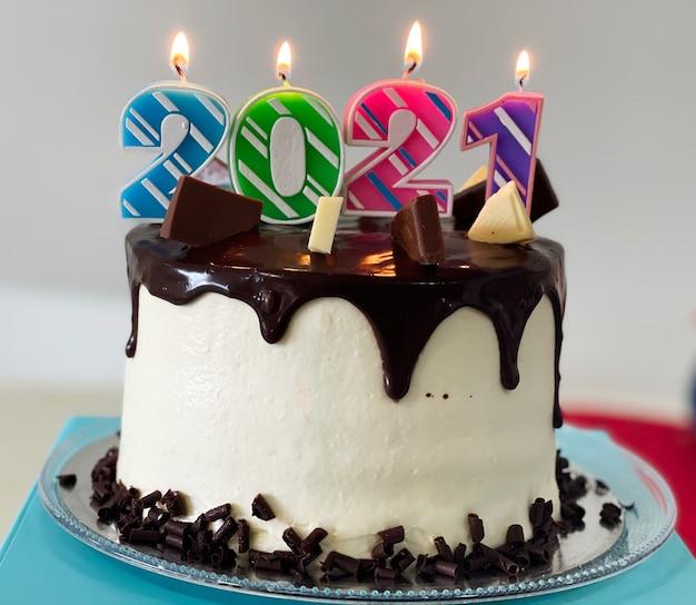 Gros plan du gâteau du nouvel an avec des bougies allumées colorées de 2021 et des stries de chocolat.