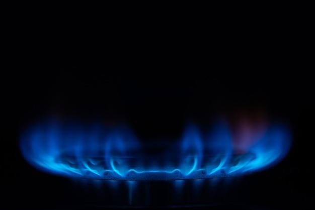 Gros plan du gaz de la cuisinière sur fond sombre