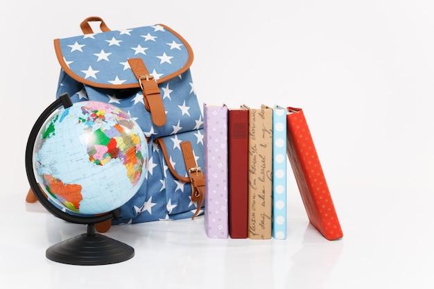 Gros plan du globe, sac à dos bleu avec impression d'étoiles et livres scolaires colorés