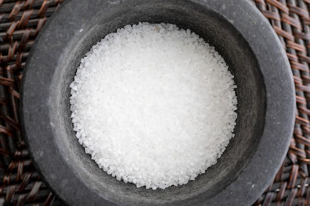 Gros plan avec du gros sel. au mortier de pierre. aspect rustique.