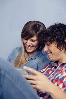 Gros plan du jeune couple amoureux à la recherche de smartphones et de rire en se reposant sur un lit. concept de temps libre à la maison.