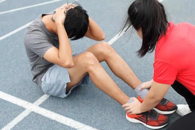 Gros plan du jeune couple asiatique faisant des sit-ups sur la piste de course bleue au stade