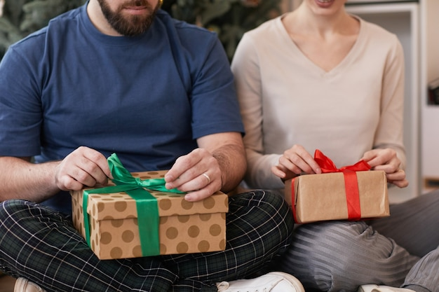 Gros plan du jeune couple assis avec les jambes croisées et déballant les cadeaux de noël en même temps