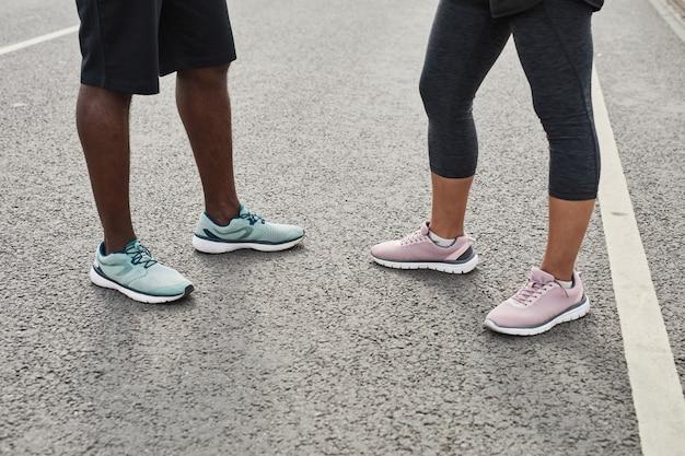 Gros plan du jeune couple en chaussures de sport se réunissant à l'extérieur pour s'entraîner ensemble