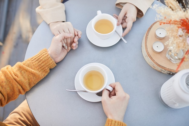 Gros plan du jeune couple main dans la main et boire du thé pendant leur rendez-vous romantique au restaurant