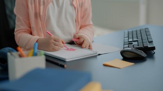 Gros plan du jeune enfant à l'aide de crayons colorés sur ordinateur portable