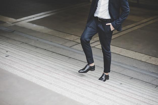 Gros plan du jeune homme d'affaires marchant à l'étage à l'extérieur du bureau.