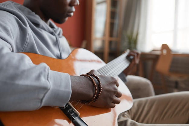 Gros plan du jeune homme afro-américain jouant de la guitare acoustique alors qu'il était assis sur le canapé et faire de la musique à la maison, copiez l'espace