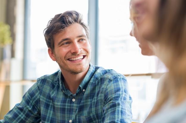 Gros plan du jeune homme gai en conversation avec une femme à la cafétéria