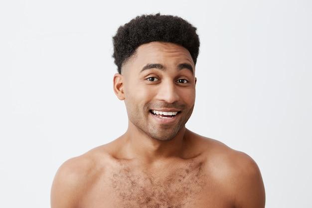 Gros plan du jeune homme séduisant de bonne humeur à la peau noire avec une coiffure afro avec un torse nu souriant avec des dents, regardant à huis clos avec une expression détendue et heureuse. santé et beauté