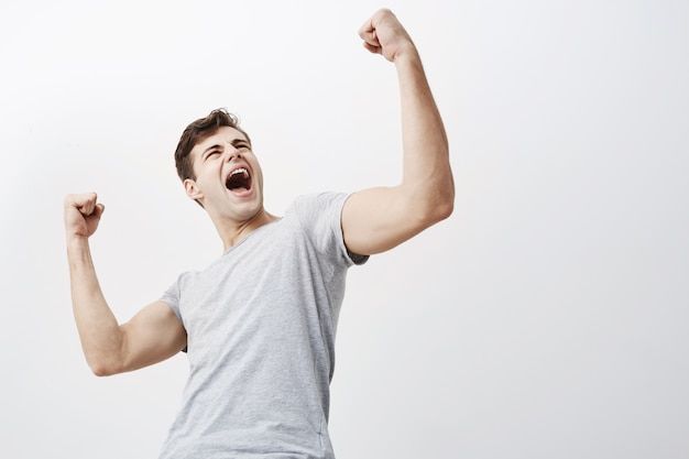 Gros plan du jeune sportif masculin caucasien réussi crier oui et lever les poings serrés dans l'air, se sentant excité. les gens, le succès, le triomphe, la victoire, la victoire et la célébration.