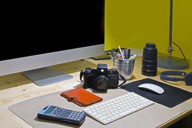Gros plan du lieu de travail avec écran d'ordinateur vierge et accessoires
