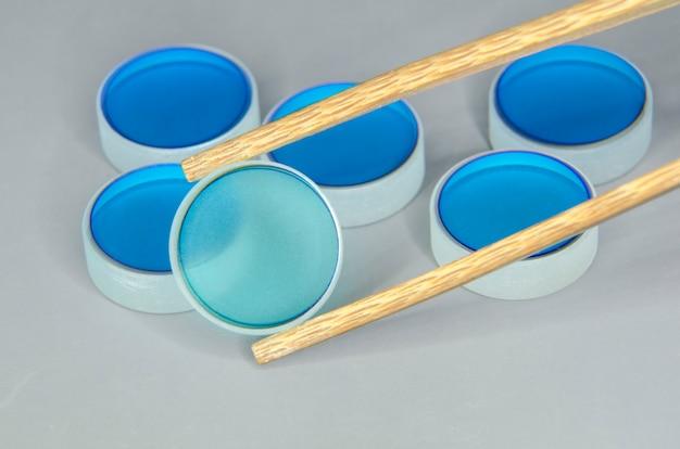 Gros plan du lot de miroirs optiques en mettant l'accent sur l'un sélectionné par une pince à épiler en bois