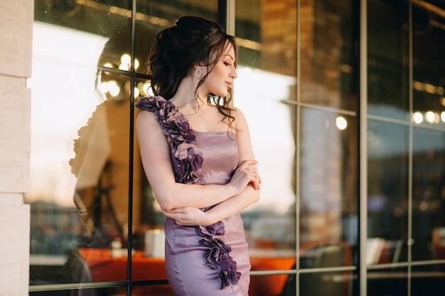 Gros plan du luxe jeune femme s'appuyant sur la fenêtre du restaurant coulissant moderne