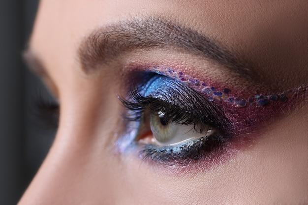 Gros plan du maquillage de soirée lumineux sur le concept de cours de maquillage pour les yeux féminins