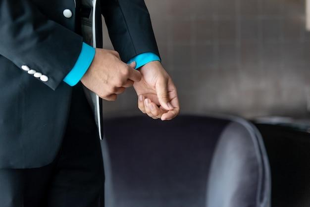 Gros plan du marié dans son smoking fixant ses boutons de manchette
