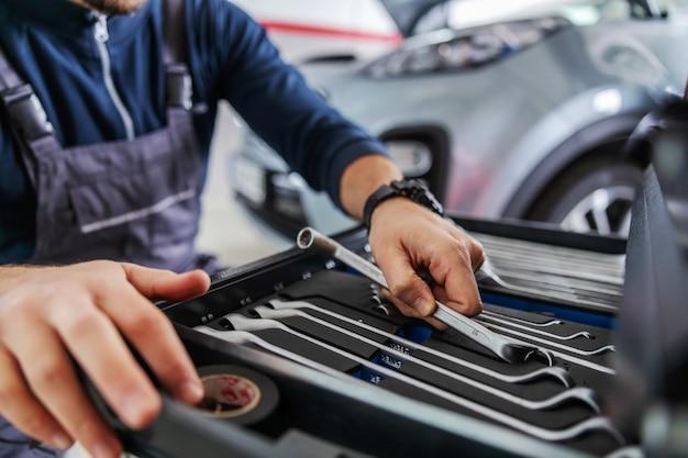 Gros plan du mécanicien tenant la clé de la boîte à outils en s'accroupissant dans le garage du salon de voiture.