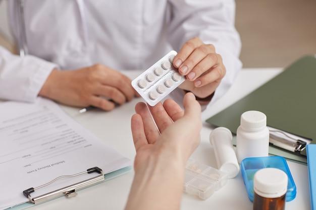 Gros plan du médecin assis à la table, donnant des pilules à son patient à l'hôpital