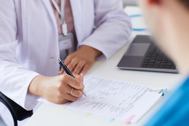 Gros plan du médecin assis à la table et remplissant le formulaire, il prescrit un médicament pour le patient