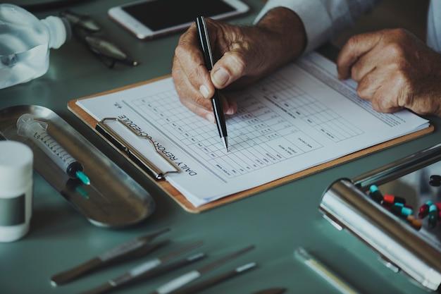 Gros plan du médecin vérifiant la liste de contrôle du rapport quotidien du patient
