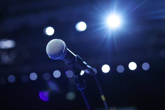 Gros plan du microphone dans la salle de concert ou la salle de conférence avec des lumières froides en arrière-plan.