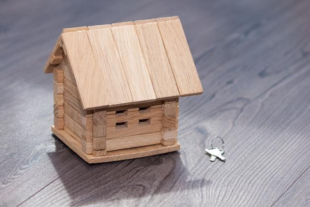 Gros plan du modèle de maison en bois et des clés d'argent sur fond en bois.