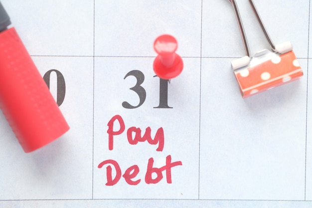 Gros plan du mot de la dette de paiement sur le calendrier