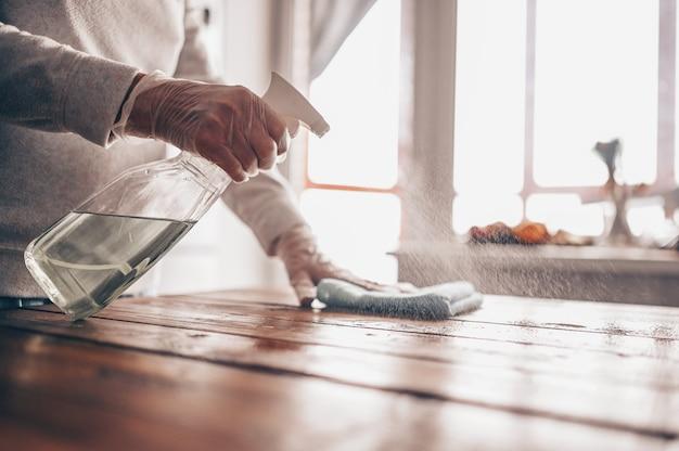 Gros plan du nettoyage de la table en bois à la maison, de la désinfection de la surface de la table de la cuisine avec un flacon pulvérisateur désinfectant antibactérien, du lavage des surfaces avec une serviette et des gants.
