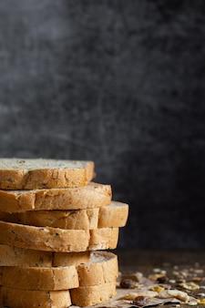 Gros plan du pain de blé entier à grains tranchés sur fond de bois rustique foncé ingrédients bio