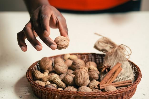 Gros plan du panier en osier avec diverses noix et cannelle en elle et main de l'homme tenant la noix