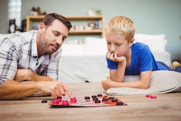Gros plan du père et du fils jouant au jeu de dame