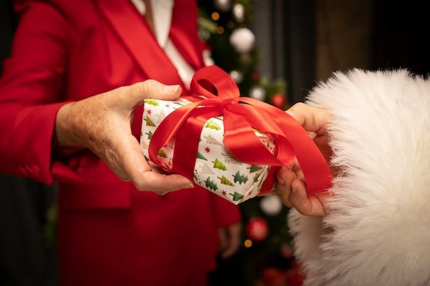 Gros plan du père noël recevant un cadeau de noël