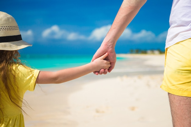 Gros plan du père et de la petite fille se tenant par la main à la plage