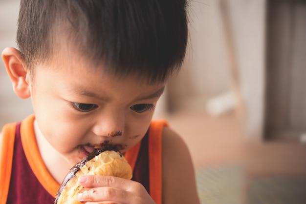 Gros plan du petit garçon affamé eaitng beignet chaud