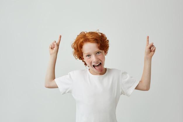 Gros plan du petit garçon drôle avec des cheveux roux bouclés et des taches de rousseur pointant vers le haut avec les deux mains, ayant le visage idiot avec la bouche ouverte. copiez l'espace.
