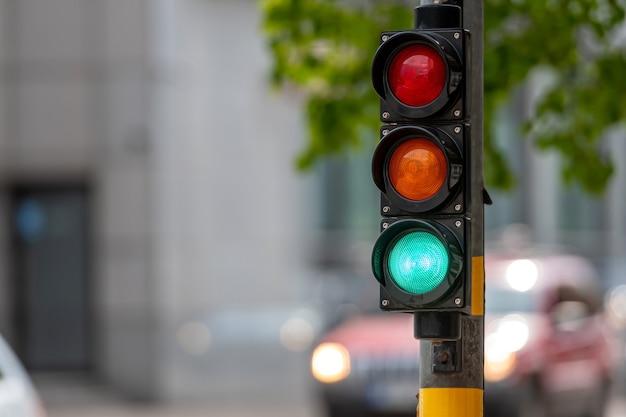 Gros plan du petit sémaphore de circulation avec feu vert dans le contexte de la circulation urbaine