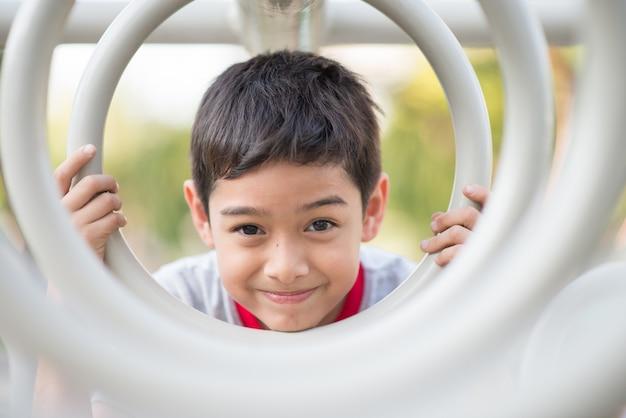 Gros plan du petit visage de garçon accroché sur la barre de cycle au terrain de jeux