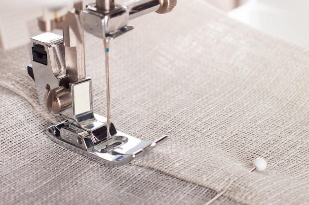 Gros plan du pied-de-biche de machine à coudre moderne et article de couture à l'aiguille de vêtements.