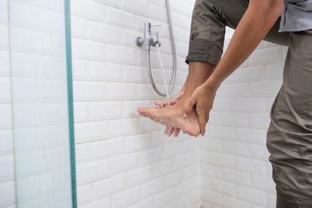 Gros plan du pied de l'homme effectuer des ablutions (wudhu) avant la prière à la maison