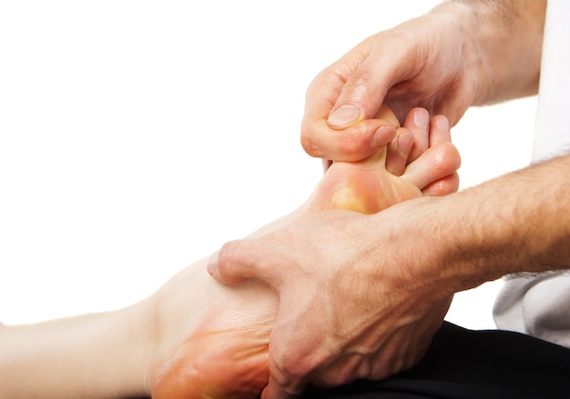 Gros plan du pied recevant un massage sur blanc