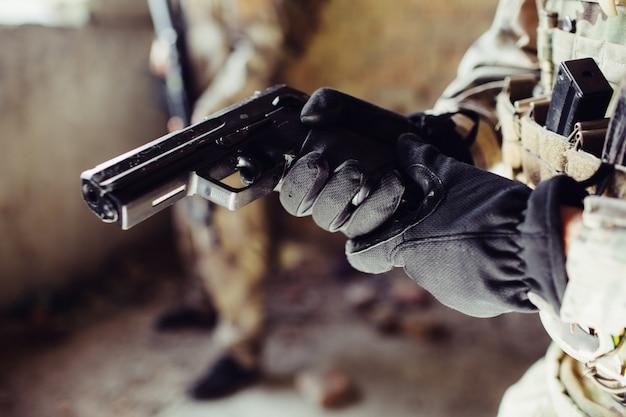 Gros plan du pistolet noir que le soldat tient.