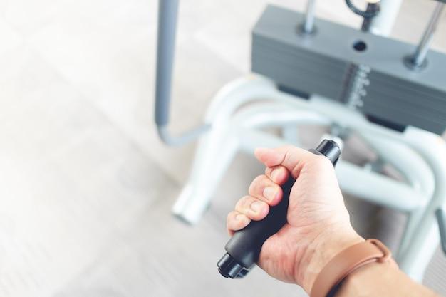 Gros plan du poids du câble de traction de la main de l'homme dans une salle de fitness.