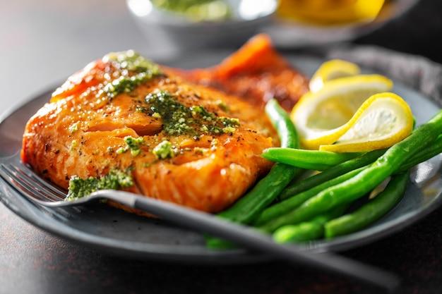 Gros plan du poisson saumon cuit au four avec des haricots verts
