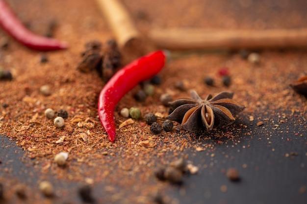 Gros plan du poivron rouge épicé, cannelle et poivre moulu se trouvent sur la table.