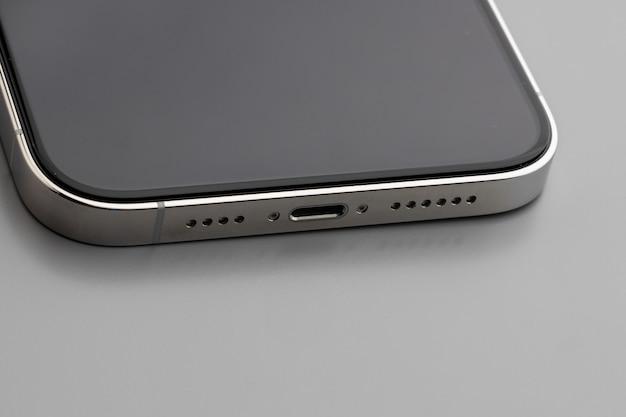Gros plan du port de chargement du smartphone moderne sur fond gris