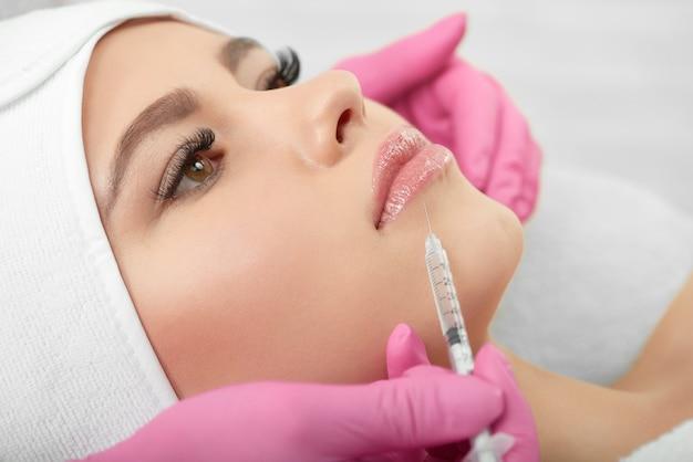 Gros plan du processus d'agrandissement des lèvres cosmétologiques.