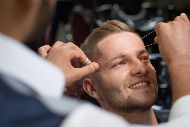 Gros plan du processus de filetage de la procédure dans un salon de coiffure