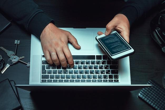Gros plan du programmeur des mains de hacker en tapant un code