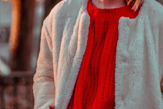 Gros plan du pull rouge et veste duveteuse blanche